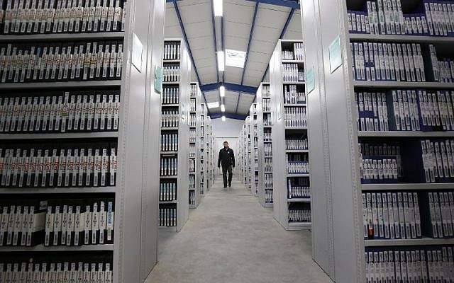 A man walks in a section of the 68 miles of shelving of TV and radio recordings of the French National Audiovisual Institute (INA) at the INA's central archive conservation in Saint Remy L'Honore, December 16, 2015. (AFP/Patrick Kovarik)
