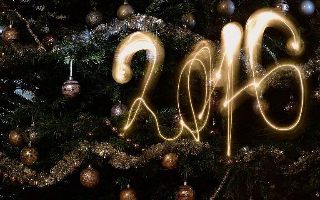 This long-exposure picture taken in Budapest on December 31, 2015 shows the new year 2016 written with a flashlight in front of a Christmas tree. (AFP/Attila Kisbenedek)