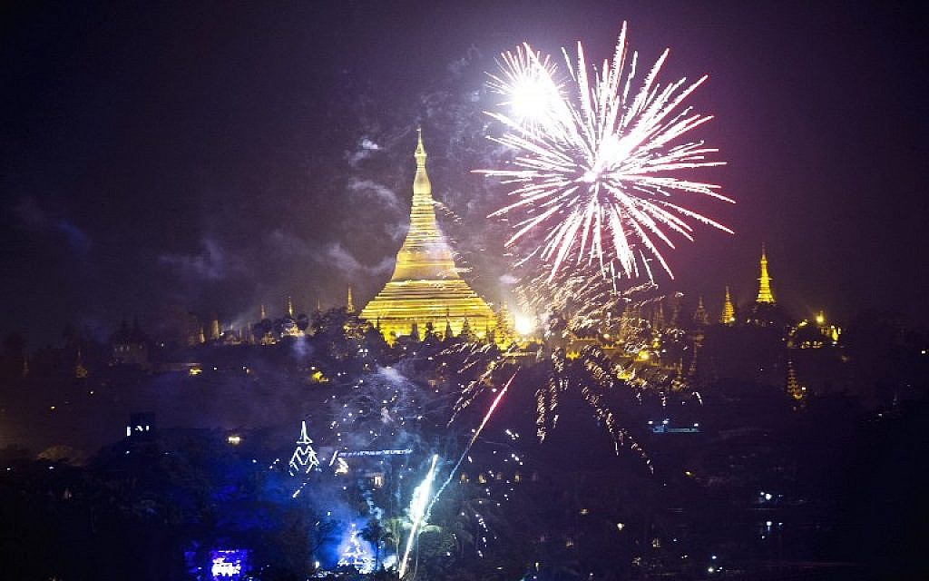 Firework are seen near the Myanmar landmark Shwedagon pagoda during the New Year countdown at the Kandawgyi Park in Yangon on January 1, 2016.  (AFP / YE AUNG THU)