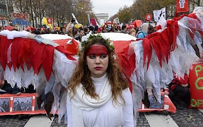 An activist joins others to form a giant red line during a demonstration near the Arc de Triomphe in Paris on December 12, 2015, as a proposed 195-nation accord on climate change is presented at a UN conference in Le Bourget. (AFP PHOTO/ALAIN JOCARD)