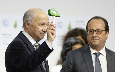 French Foreign Affairs Minister and President-designate of COP21 Laurent Fabius (L) waves the official gavel of the UN climate conference, as President Francois Hollande looks on, after adoption of a historic global warming pact in Bourget, north of Paris, on December 12, 2015. (AFP PHOTO/FRANCOIS GUILLOT)