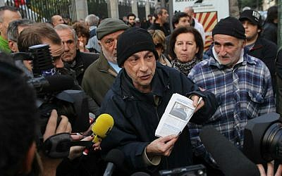 A man shows a newspaper article about Christmas Eve's clash in which two firefighters and a police officer were injured at the poor Jardins de l'Empereur housing estate, to journalists during a demonstration in Ajaccio, Corsica on December 27, 2015, after France banned demonstrations in part of the Corsican capital following two days of anti-Arab protests and sectarian tensions. (AFP/Yannick Graziani)
