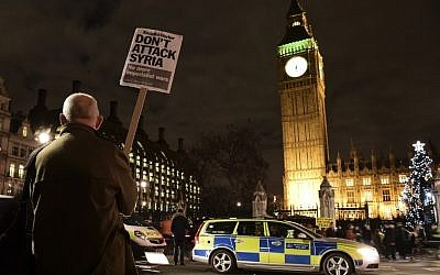 A protester holds a placard reading 'Don't attack Syria' during a demonstration against British military action in Syria outside the Houses of Parliament in London, December 1, 2015. (Photo by AFP Photo / Leon Neal)