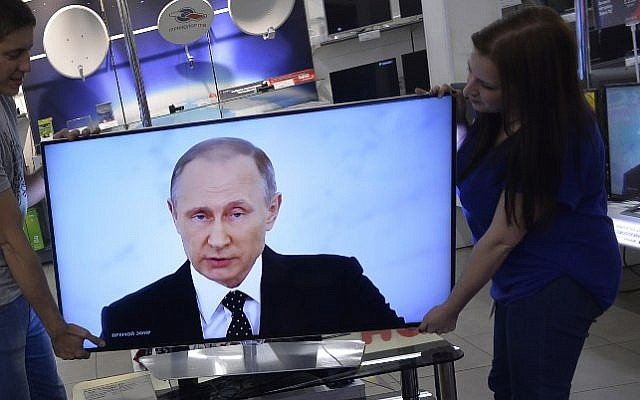 Shop assistants install a TV set at a shop in Moscow on December 3, 2015 during the broadcast of Russian President Vladimir Putin's annual state of the nation address. (AFP/Natalia Kolesnikova)