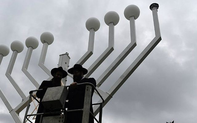 Two rabbis stand on a elevated platform as a giant eight-branched Hanukkah candelabrum is installed in front of the Brandenburg Gate in Berlin on December 4, 2015, two days before the start of the eight-day Jewish holiday. (AFP Photo/Tobias Schwarz)