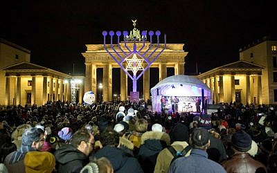 People stand in front of a giant eight-branched Hanukkah candelabrum in front of the Brandenburg Gate in Berlin on December 6, 2015 at the start of the eight-day Jewish holiday. (AFP Photo/DPA/Jorg Carstensen)