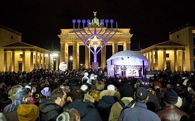 People stand in front of a giant menorah in front of the Brandenburg Gate in Berlin on December 6, 2015. (Jorg Carstensen/DPA/AFP)