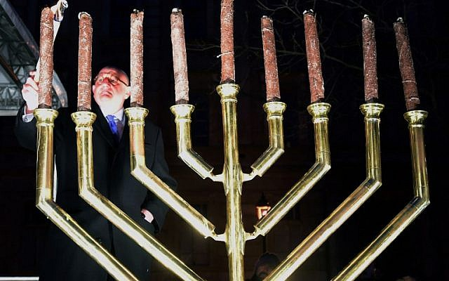 Ira Forman (L), Special Envoy of the US government to Monitor and Combat Antisemitism lights a torch on the last day of Hanukkah in Szekesfehervar on December 13, 2015, during a joint commemoration for Hanukkah and a silent demonstration to protest against plans for a statue in honor of anti-Semitic Holocaust-era lawmaker Balint Homan. (AFP PHOTO/ATTILA KISBENEDEK)