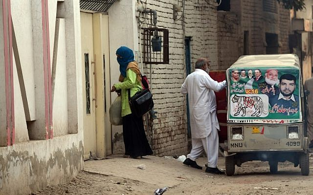 An unidentified woman and elderly man leave the house of Gulzar Ahmed Malik, the father of female US shooter Tashfeen Malik, after Pakistani investigators examined the house in Multan, December 6, 2015. (AFP/FAROOQ NAEEM)