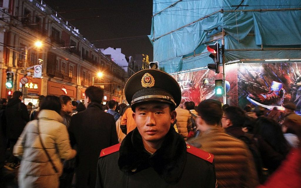 """A security officer on patrol on New Year's Eve on the historic riverfront, known as """"the Bund,"""" in Shanghai on December 31, 2015. (AFP Photo/STR)"""