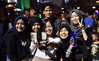 Indonesians take a selfie photograph as they gather during a countdown event to celebrate the New Year in Jakarta on December 31, 2015.  (AFP PHOTO / Bay ISMOYO)