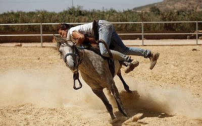 Druze horsewoman and trainer Rajaa Kheir battles to saddle a stray horse on September 17, 2015, at her ranch in the Druze town of Majdal Shams, in the southern foothills of Mount Hermon, north of the Golan Heights. (AFP/JALAA MAREY)