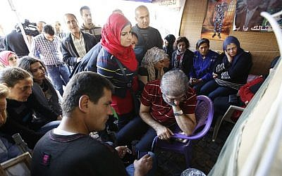 Relatives of Lebanese soldiers and policemen kidnapped by jihadist groups in early August 2014 in the eastern border town of Arsal, watch news reports about the anticipated release of their loved ones in a tent erected outside the government's offices in downtown Beirut, November 29, 2015. (Photo by AFP Photo/Anwar Amro)