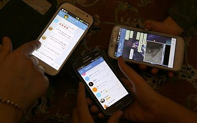 Iranians display their smartphones using the Telegram messenger application on December 1, 2015. (AFP Photo/Atta Kenare)