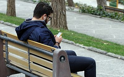 An Iranian man uses a smartphone at a park in Tehran on December 1, 2015. (AFP PHOTO / ATTA KENARE / AFP / ATTA KENARE)