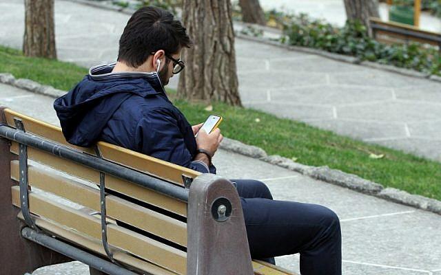 An Iranian man uses a smartphone at a park in Tehran on December 1, 2015. (AFP PHOTO / ATTA KENARE / AFP / ATTA KENARE)