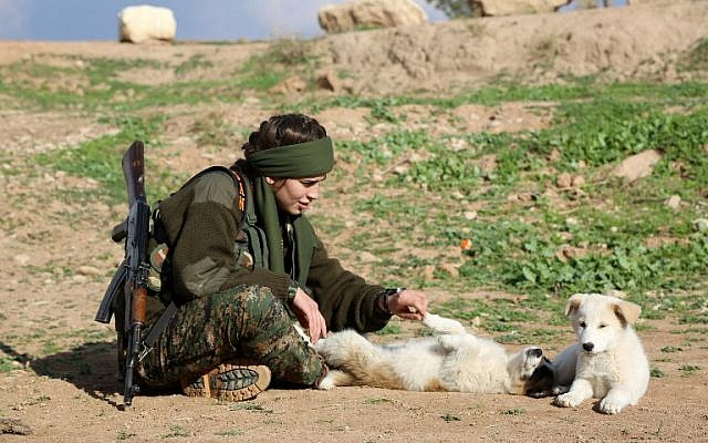 "Syriac Christian Lucia, member of the battalion called the ""Female Protection Forces of the Land Between the Two Rivers"" fighting the Islamic State group, plays with a dog during a training on December 1, 2015 at their camp in the town of al-Qahtaniyah, near the Syrian-Turkish border (aka Kabre Hyore in Syriac, and Tirbespi in Kurdish).(AFP PHOTO / DELIL SOULEIMAN / AFP / DELIL SOULEIMAN0)"