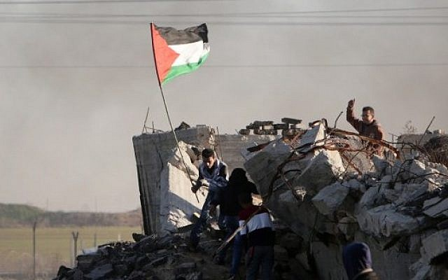 File: A Palestinian protester holds a national flag during clashes with Israeli security forces along the border with Israel in the eastern suburbs of Gaza City on December 4, 2015.(AFP PHOTO/MAHMUD HAMS)