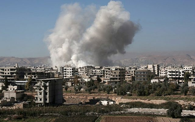 Smoke billows from buildings following a reported air strike in Damascus' rebel-held suburb of Zamalka on December 6, 2015. (AFP/AMER ALMOHIBANY)