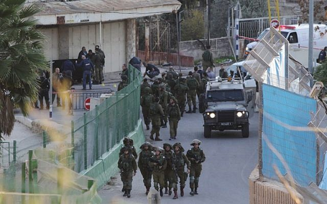 File: Israeli security forces gather at the site where a Palestinian stabbed an Israeli near the Tomb of the Patriarchs in Hebron, on December 7, 2015. (AFP/Hazem Bader)