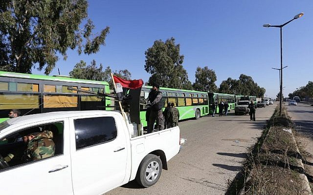 Syrian government forces escort buses carrying Syrian rebel fighters as hundreds of civilians and rebel forces began evacuating the last opposition-held district of Waer in the central city of Homs, under a deal with the Syrian regime, December 9, 2015. (Photo by AFP Photo/Louai Beshara)