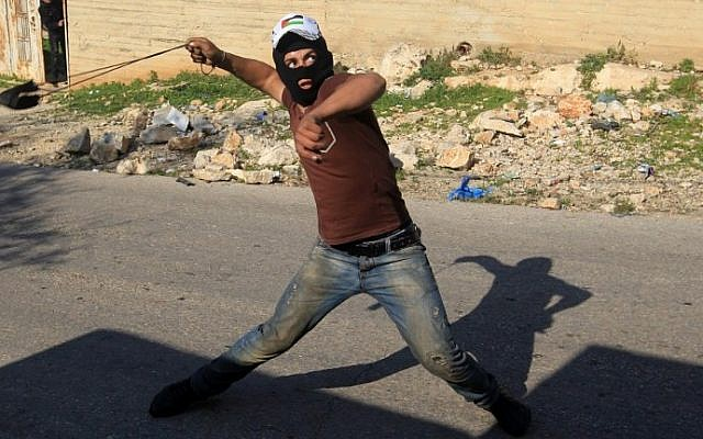 A Palestinian protester uses a slingshot to hurl rocks towards Israeli security forces during clashes near Nablus on December 11, 2015 (AFP/Jaafar Ashtiyeh)