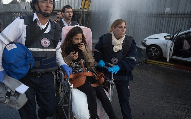 Members of Magen David Adom rescue service attend to a young woman hurt when a Palestinian terrorist drove his car into a crowd at a bus stop in Jerusalem on December 14, 2015, wounding 14 people. (AFP PHOTO/MENAHEM KAHANA)