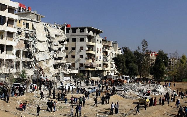 Syrians gathering at the site of a reported Israeli airstrike that killed senior Hezbollah terrorist Samir Kuntar in Damascus, December 20, 2015. (AFP/Louai Beshara)