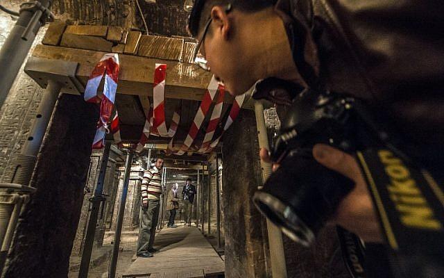 A photographer looks through the entrance of the tomb of Maia, the wet-nurse of legendary Egyptian boy king Tutankhamun, in Saqqara, Egypt, on December 20, 2015. (AFP/KHALED DESOUKI)