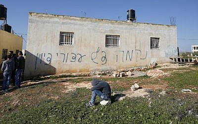 Palestinians gather next to a house sprayed with graffiti reading in Hebrew: 'revenge' and 'hello from the prisoners of Zion,' in the West Bank village of Beitillu on December 22, 2015.(AFP PHOTO/ABBAS MOMANI)