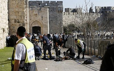 Israeli forensic police stand next to the body of a Palestinian attacker who was shot dead as he stabbed Israelis outside the Jaffa Gate of the Old City, Jerusalem December 23, 2015. (AFP/AHMAD GHARABLI)