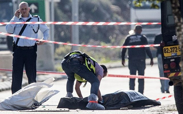 An Israeli forensic policeman stands next to the body of a Palestinian assailant who was shot dead after he stabbed two Israeli security guards at the Barkan Industrial Zone next to the settlement of Ariel, December 24, 2015. (Phot by AFP Photo/Jack Guez)