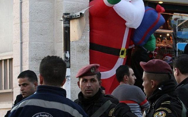 Palestinian security forces and military medical services stand guard outside the Church of the Nativity as Christians gather for Christmas celebrations in the West Bank city of Bethlehem, on December 24, 2015. (AFP/Musa al-Shaer)