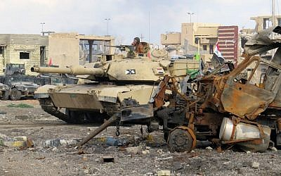 Iraqi counterterrorism forces drive a tank past rubble south of the Anbar province's capital of Ramadi, on December 24, 2015. (AFP/STR)