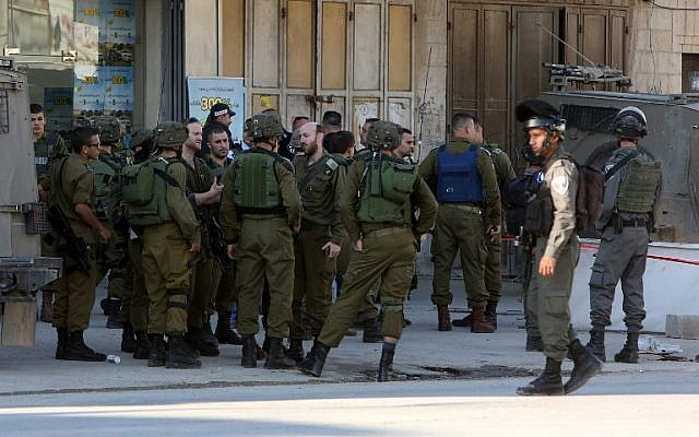Illustrative. Israeli security forces gather at the site of a reported stabbing attack near the Hawara checkpoint near the West Bank city of Nablus, on December 27, 2015. (AFP/Jaafar Ashtiyeh)