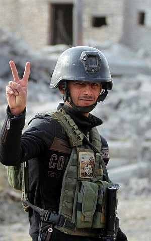 A member of Iraq's elite counter-terrorism service flashes the V for victory sign on December 27, 2015 in the Hoz neighbourhood in central Ramadi, during military operations against the Islamic State. (AFP PHOTO/AHMAD AL-RUBAYE)