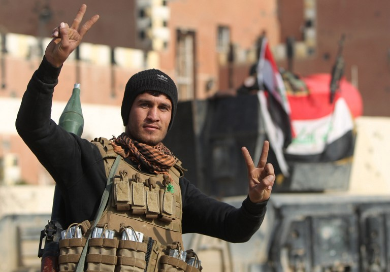 A member of Iraq's elite counterterrorism service flashes the 'V' for 'Victory' sign after Iraqi forces recaptured the city of Ramadi from the Islamic State, December 28, 2015. (AFP/Ahmad al-Rubaye)