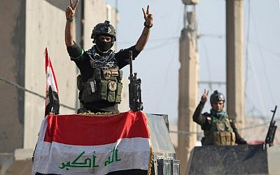 "Members of Iraq's elite counter-terrorism service flash the ""V"" for victory sign on December 29, 2015 in the city of Ramadi after Iraqi forces recaptured it from the Islamic State jihadist group. AFP/Ahmad al-Rubaye)"