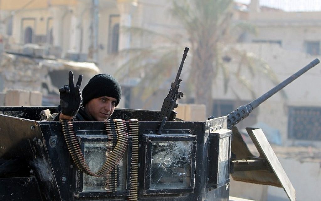 A member of Iraq's elite counter-terrorism service flashes the 'V' for victory sign on December 29, 2015 in the city of Ramadi, the capital of Iraq's Anbar province, about 110 kilometers west of Baghdad, after Iraqi forces recaptured it from the Islamic State jihadist group. (AFP Photo/Ahmad Al-Rubaye)