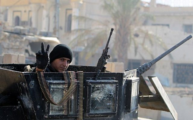 A member of Iraq's elite counter-terrorism service flashes the 'V' for victory sign on December 29, 2015 in the city of Ramadi, the capital of Iraq's Anbar province, about 110 kilometers west of Baghdad, after Iraqi forces recaptured it from the Islamic State (IS) jihadist group. (AFP PHOTO / AHMAD AL-RUBAYE)