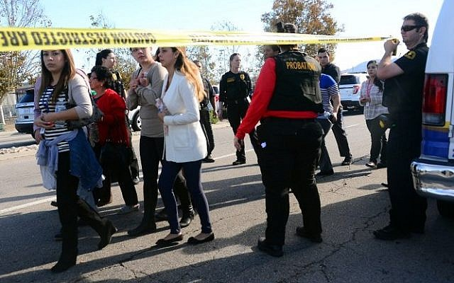 Survivors are evacuated from the scene of a shooting under police and sheriff escort on December 2, 2015 in San Bernardino, California.  (AFP PHOTO/FREDERIC J. BROWN)