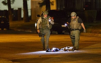 Law enforcement officers investigate a suspicious bag, later found not to be a threat, on Victoria Avenue after a mass shooting at the Inland Regional Center on Wednesday, December 2, 2015 in San Bernardino, California. (AFP PHOTO / PATRICK T.  FALLON)