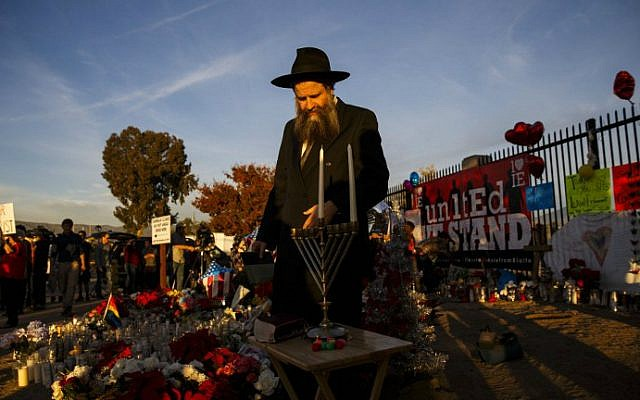 Rabbi Sholom Harlig prepares to light the menorah for the first night of Hanukkah at a makeshift memorial near the Inland Regional Center in the aftermath of a mass terror shooting that killed 14 people on Sunday, December 6, 2015 in San Bernardino, California. (AFP Photo/Patrick T. Fallon)