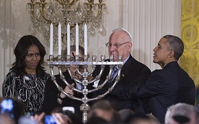 US President Barack Obama helps Israeli President Reuven Rivlin light the menorah during a Hanukkah reception at the White House in Washington, DC, December 9, 2015. (Photo by AFP Photo/Jim Watson)