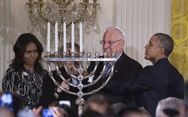 US President Barack Obama helps Israeli President Reuven Rivlin light the menorah during a Hanukkah reception at the White House in Washington, DC,  December 9, 2015. (Photo by AFP Photo/Jim Watson)