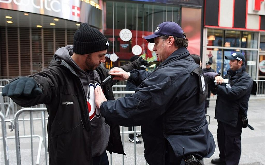 A New York City police officer inspects a reveler joining the crowd in Times Square on December 31, 2015 in New York. (AFP PHOTO/DON EMMERT)
