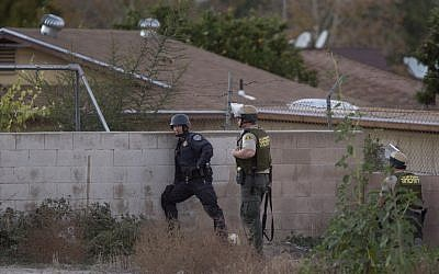 Law enforcement officers search for a possible suspect following a shootout with suspects of a mass shooting at the Inland Regional Center by multiple gunmen on December 2, 2015 in San Bernardino, California. (David McNew/Getty Images/AFP)