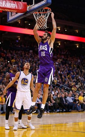 Omri Casspi #18 of the Sacramento Kings dunks the ball over Stephen Curry #30 of the Golden State Warriors at ORACLE Arena on December 28, 2015 in Oakland, California (Ezra Shaw/Getty Images/AFP)
