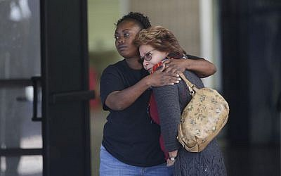 Two women embrace at a community center where family members are gathering to pick up survivors after a shooting rampage that killed multiple people and wounded others at a social services center in San Bernardino, California, Wednesday, Dec. 2, 2015. (AP/Jae C. Hong)