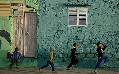 In this Saturday Dec. 19, 2015 photo, Palestinian boys run by a painted house in the Shati Refugee Camp in Gaza City. (AP Photo/Hatem Moussa)